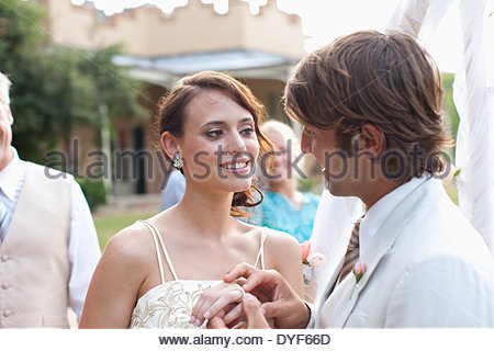 Groom putting ring on brideÂ's finger - Stock Photo