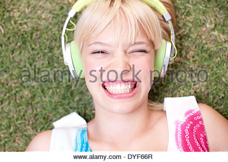 Woman laying on grass listening to headphones - Stock Photo