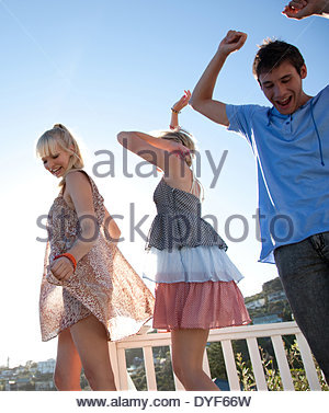 Friends dancing on rooftop - Stock Photo