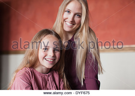 Portrait of smiling mother and daughter hugging - Stock Photo