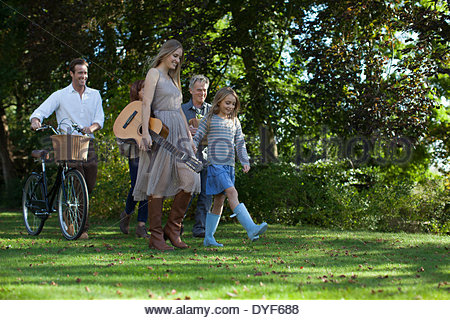 Multi-generation family bicycle, apples guitar in orchard - Stock Photo
