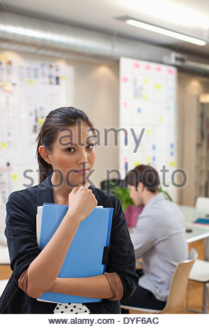 Portrait of  businesswoman with folders in office - Stock Photo