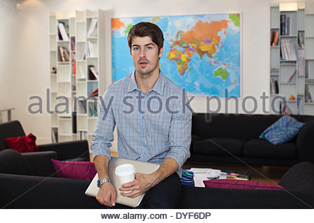 Portrait of  businessman with coffee cup in office - Stock Photo