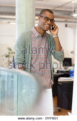Businessman paperwork talking on cell phone in office - Stock Photo