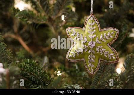 A green star Christmas Ornament hangs on a lit Christmas Tree. - Stock Photo