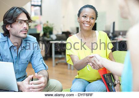 Businesswomen handshaking in meeting - Stock Photo