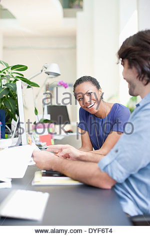 Businessman businesswoman discussing paperwork in office - Stock Photo