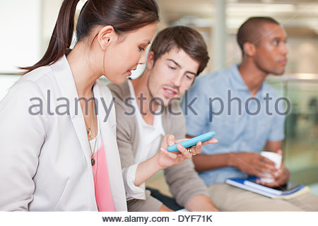 Businesswoman text messaging on cell phone in office - Stock Photo