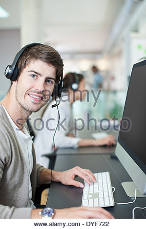 Businessman headphones working computer in office - Stock Photo