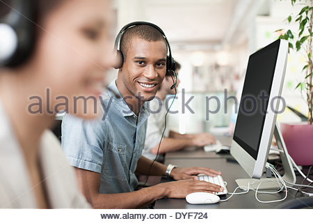 Portrait smiling businessman headset computer in office - Stock Photo
