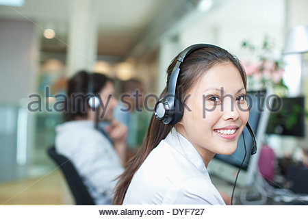 Portrait smiling businesswoman headset computer in office - Stock Photo