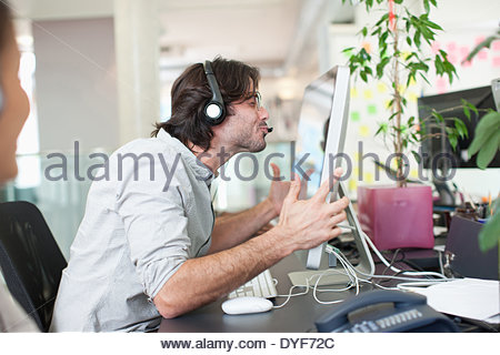 Business people headsets working computers in office - Stock Photo