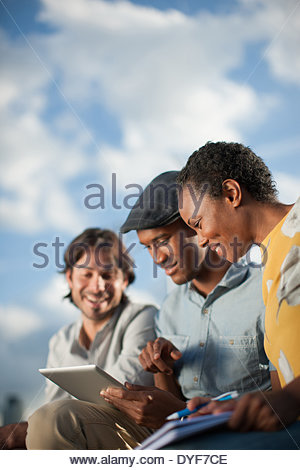 Business people sharing digital tablet in meeting - Stock Photo