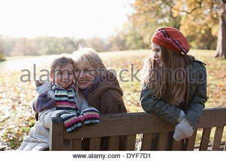 Grandmother hugging granddaughter outdoors - Stock Photo