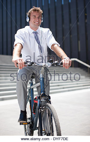 Businessman in headphones sitting on bicycle - Stock Photo