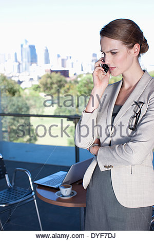 Businesswoman talking on cell phone in cafe - Stock Photo