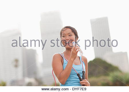 Woman drinking water after exercise - Stock Photo