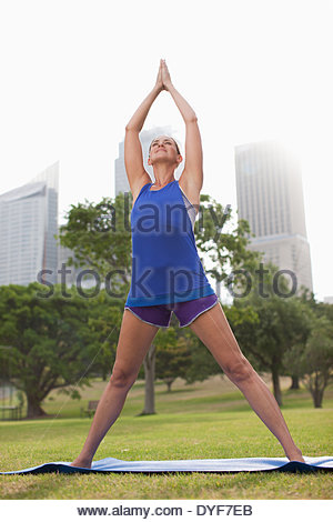 Woman practicing yoga in park - Stock Photo