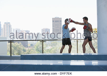 Boxer training with coach outdoors - Stock Photo