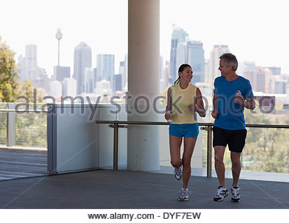 Couple running in urban setting - Stock Photo