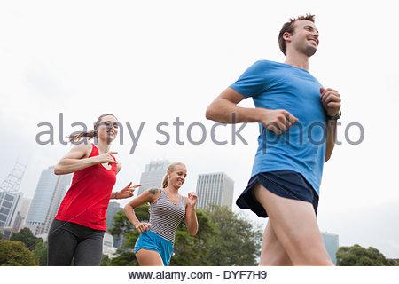Friends running in urban park - Stock Photo