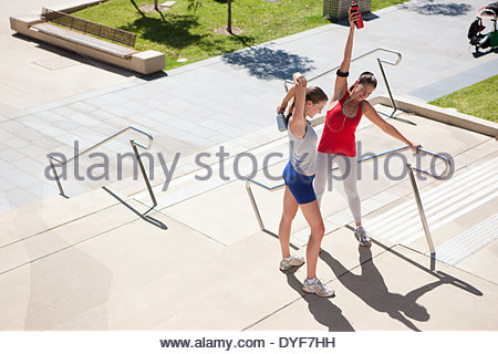 Friends stretching on park bench - Stock Photo