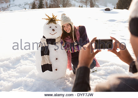 Man taking picture of girlfriend and snowman - Stock Photo