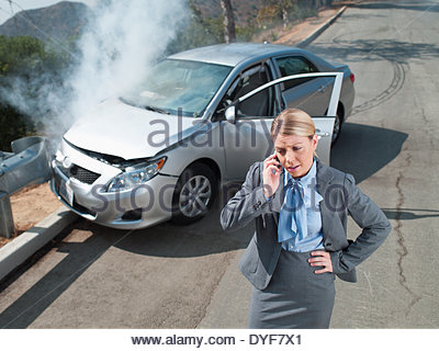 Businesswoman using cell phone near car wrecked on guardrail - Stock Photo