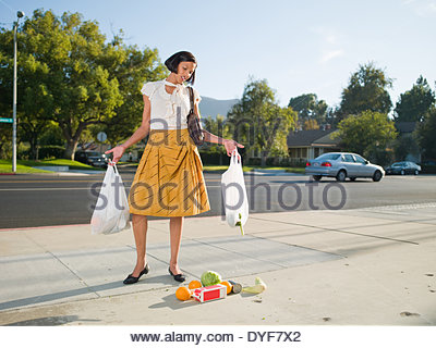 Frustrated woman dropping groceries on sidewalk - Stock Photo