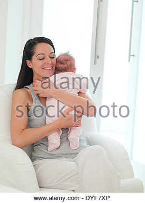 Smiling mother holding baby - Stock Photo