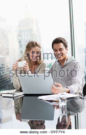 Business people using laptop together - Stock Photo