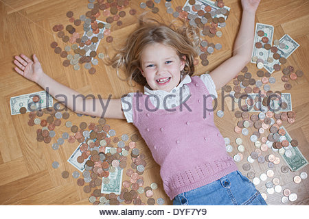 Girl laying on floor with coins - Stock Photo