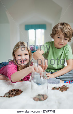 Brother sister playing counting money in bedroom - Stock Photo