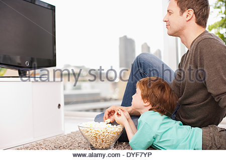 Father and son watching television - Stock Photo