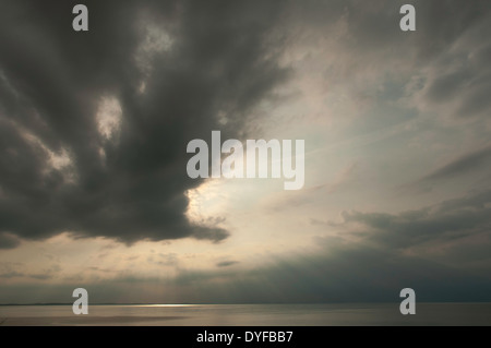 Ominous clouds obscure the setting sun over Ipswich Bay in Massachusetts - Stock Photo
