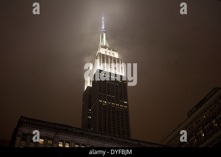 The art-deco architecture of New York's Empire State Building at night in a snowstorm