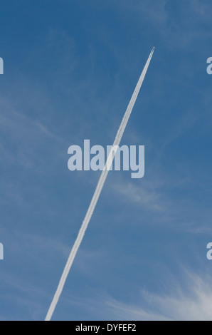 Condensation trail of an airplane in blue sky - Stock Photo
