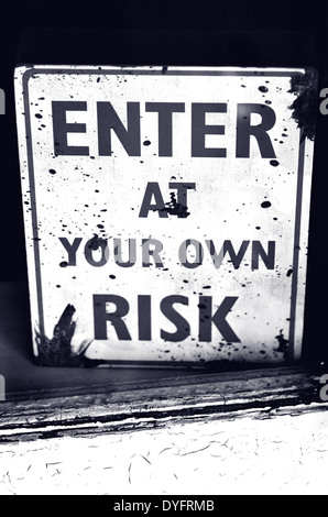 Buissness sign 'enter at your own risk' on shop display window. - Stock Photo
