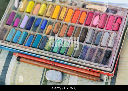 Panel set of used colorful chalk colors with pencils and rubber on artist chair. - Stock Photo