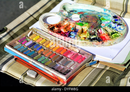 Used colorful chalk colors and colors pallet on artist chair. - Stock Photo