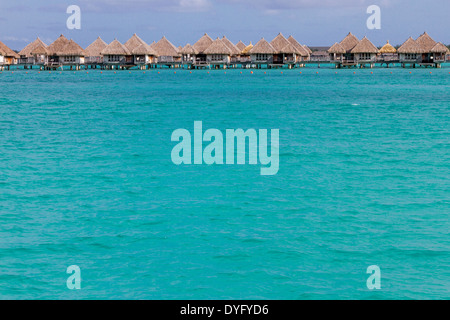Overwater bungalows over turquoise water in Bora Bora in French Polynesia - Stock Photo