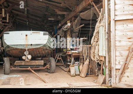 Interior view of an old boat yard workshop, showing a small dinghy with tools and equipment. - Stock Photo