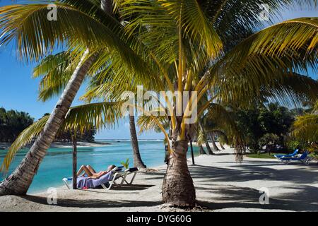 Aitutaki. Cook Island. Polynesia. South Pacific Ocean. Some tourists take a sun bath on the beach of Aitutaki Lagoon - Stock Photo