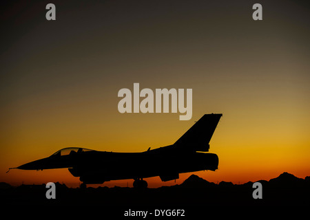 A US Air Force F-16C Fighting Falcon aircraft sits on the aircraft parking ramp at sunset April 13, 2014 at Davis - Stock Photo