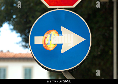 Graffiti on road traffic sign with euro coin, Florence, Italy - Stock Photo