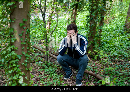 A depressed man sit alone in the woods with head in hands - Stock Photo