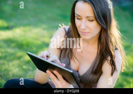 Frau sitzt mit Tablet in der Wiese - woman with tablet in the meadow - Stock Photo