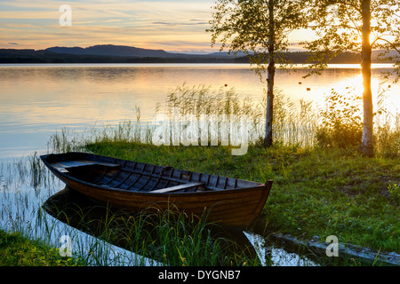 Wooden boat at the lakeside at sunset, Solleron, Dalarna, Sweden - Stock Photo