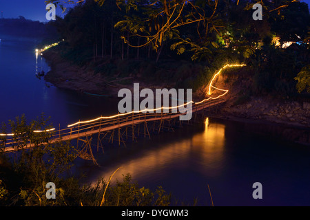 Wooden  bamboo suspension bridge over Nam khan river in Luang Prabang, early evening ,Laos - Stock Photo