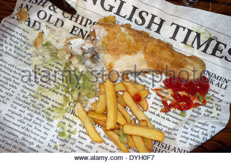 A nearly finished portion of battered cod, chips & mushy peas, plus ketchup, served on newspaper style wrapping - Stock Photo